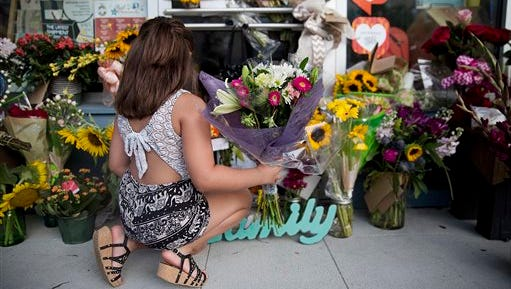 """A young girl leaves flowers in front of the Red Arrow Workshop, a memorial dedicated to shooting victim Jillian Johnson following a deadly shooting at the The Grand 16 theater, Friday, July 24, 2015, in Lafayette, La. John Russell Houser stood up about 20 minutes into Thursday night's showing of """"Trainwreck"""" and fired on the audience with a semiautomatic handgun."""