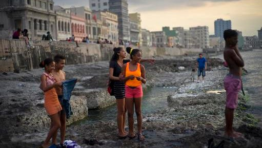 FILE - In this March 18, 2016 file photo, youths spend the afternoon along Havana's Malecon seawall, in Cuba. Cuba's President Raul Castro said on state television that his older brother Fidel Castro died late Friday, Nov. 25, 2016. He was 90.