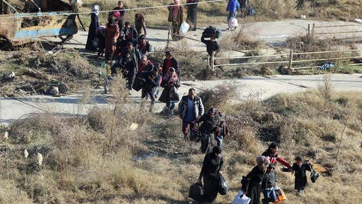This photo provided by the Rumaf, a Syrian Kurdish activist group, which has been authenticated based on its contents and other AP reporting, in a Sunday, Nov. 27, 2016 photo, shows people fleeing rebel-held eastern neighborhoods of Aleppo into the Sheikh Maqsoud area that is controlled by Kurdish fighters, Syria. Syrian state media is reporting that government forces have captured the eastern Aleppo neighborhood of Sakhour, putting much of the northern part of Aleppo's besieged rebel-held areas under state control.