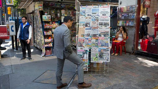 A man stops to read headlines, many featuring U.S. President Donald Trump's actions to jumpstart construction on a promised border wall and his insistence that Mexico will foot the bill, in Mexico City, Thursday, Jan. 26, 2017. Mexico's President Enrique Pena Nieto on Thursday cancelled a planned Jan. 31 meeting with Trump, hours after Trump tweeted that the meeting should be scrapped if Mexico won't pay for the wall.
