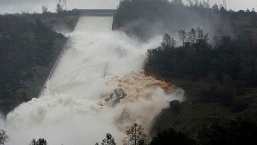 "Water flows through break in the wall of the Oroville Dam spillway, Thursday in Oroville. The torrent chewed up trees and soil alongside the concrete spillway before rejoining the main channel below. Engineers don't know what caused what state Department of Water Resources spokesman Eric See called a ""massive"" cave-in that is expected to keep growing until it reaches bedrock. (AP Photo/Rich Pedroncelli)"