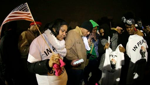 Protesters listen to the announcement of the grand jury decision Monday, Nov. 24, 2014, in Ferguson, Mo. A grand jury has decided not to indict Ferguson police officer Darren Wilson in the death of Michael Brown, the unarmed, black 18-year-old whose fatal shooting sparked sometimes violent protests.