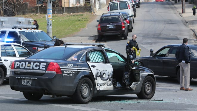 Yonkers police begin their accident investigation after two police officers were injured in a T-bone crash on Nepperhan Avenue and School Street in the city on Saturday.