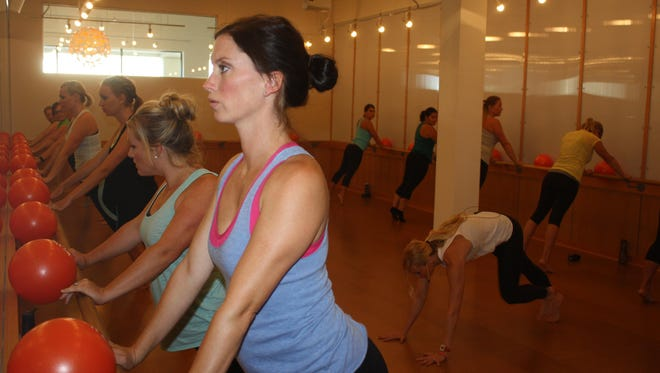 Cory Ruschman exercises at a ballet barre with members of the Fort Thomas Moms Club.