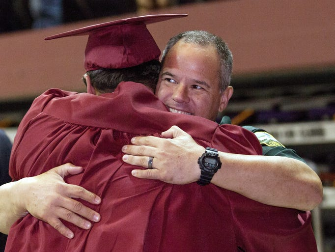 School Resource Officer Paul Emmons hugs Stephen Wright after the Lawton Chiles High School graduation ceremony on Saturday, May 31, 2014 in Tallahassee, Fla.