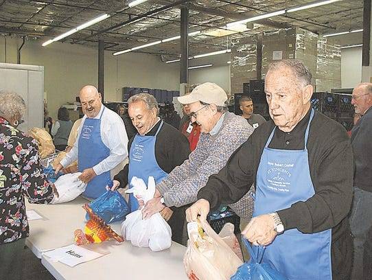 Reno Mayor Bob Cashell, Sparks Mayor Geno Martini, and CCSNN Board Member Tom Dolan help distribute turkeys at St. Vincent's Food Pantry in 2008.