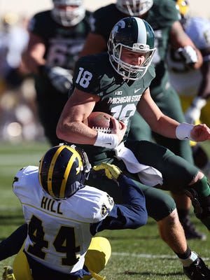 Michigan State QB Connor Cook runs over Michigan DB Delano Hill during MSU's win Saturday in East Lansing.