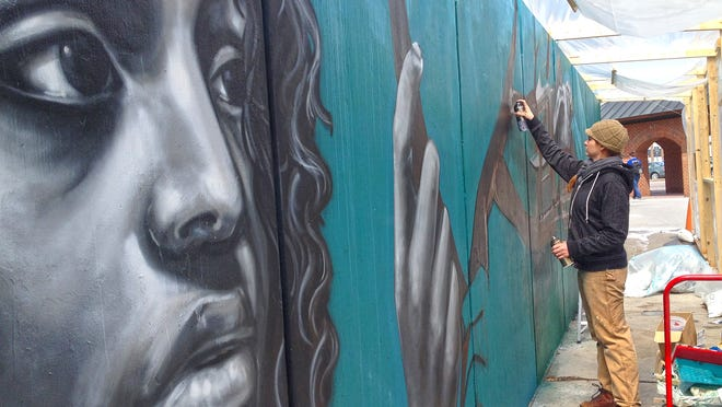 Artist Sarah C. Rutherford spray-paints a mural outside of the University of Vermont's Living/Learning Center on Thursday.