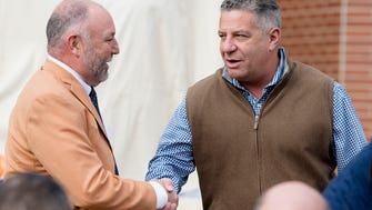 Steven Leath, Auburn University president, left, greets Bruce Pearl, Auburn Mens Basketball coach, during the unveiling of the Charles Barkley Statue before the Iron Bowl NCAA football game between Auburn and Alabama on Saturday, Nov. 25, 2017, in Auburn, Ala.