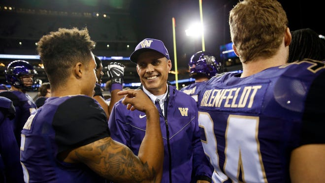 Oct 7, 2017: Washington Huskies head coach Chris Petersen celebrates with his players after a win against the California Golden Bears at Husky Stadium.