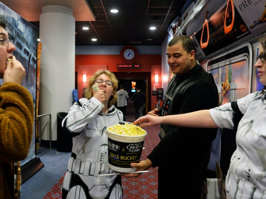 "Ricky Sharpe of Lower Paxton Township, second from right, shares popcorn with Jason Unger of York Township, Sharpe's girlfriend Ariel Grove of Fawn Township and Unger's wife Megan before the premiere of ""Star Wars: The Force Awakens"" on Thursday, Dec. 17, 2015, at Frank Theatres in York Township. The movie is the first ""Star Wars"" film since the Walt Disney Company acquired Lucasfilm in Oct. 2012. Like many other theatres nationwide, Frank Theatres prohibited masks and toy weapons, but the Force was strong with many fans who arrived costumed or wearing themed clothing."