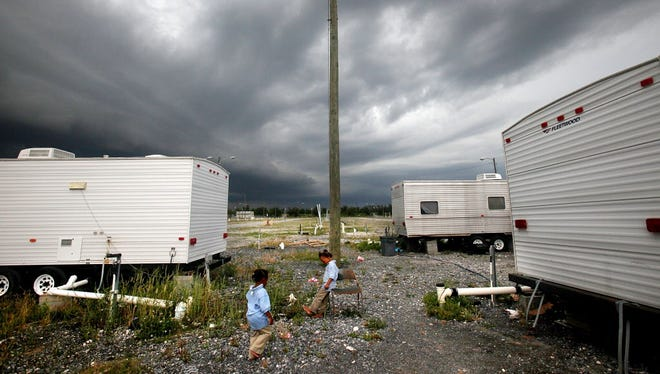 Members of the Barthelemy family gather outside their Federal Emergency Management Agency trailer on May 11, 2009, in Port Sulphur, La. Seven children from the family were living in the trailer after their home was destroyed by Hurricane Katrina.