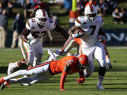 Nov 12, 2016; Charlottesville, VA, USA; Miami Hurricanes running back Gus Edwards (7) carries the ball as Virginia Cavaliers safety Juan Thornhill (21) attempts the tackle in the second quarter at Scott Stadium. The Hurricanes won 34-14. Mandatory Credit: Geoff Burke-USA TODAY Sports