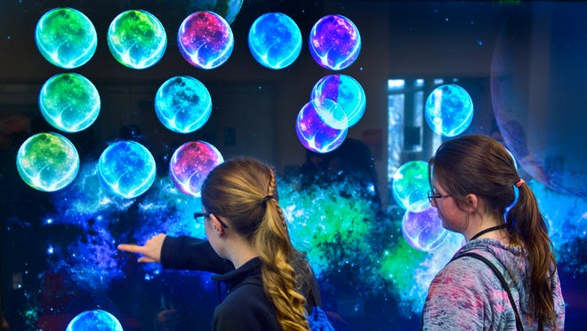 Melrose Middle School sixth-graders Grace Petersen, left, and Yasmine Crowe experiment with a program on a giant touch screen in the Visualization Research Lab Saturday, April 9, at the Integrated Science and Engineering Laboratory Facility  (ISELF) at St. Cloud State University. The workshop was part of Tech Savvy, an American Association of University Women sponsored STEM program geared toward girls in sixth through ninth grade.