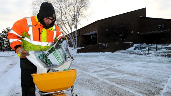 City of Mount Clemens Maintenance Department employee Josh Houston, 26, of Marine City, salts the sidewalk in front of the Mount Clemens Community Center at 300 Groesbeck, Tuesday morning, January 30, 2018.