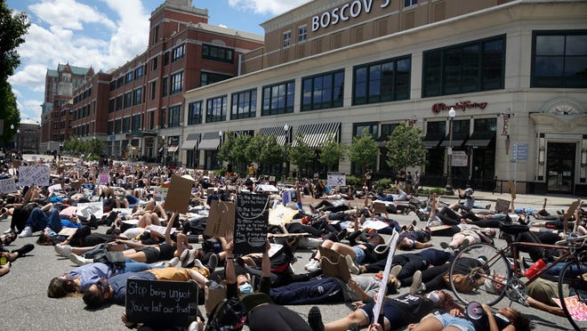 """Participants in Sunday afternoon's march """"drop dead"""" for 8 minutes and 46 seconds --the length of time a Minneapolis police officer held his knee on the neck of George Floyd -- across Francis Street in front of the Providence Place mall."""