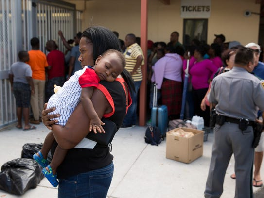 Residents wait patiently outside of Lely High School,