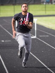 Eliyahu Young practices his handoff technique on Central's track during practice on Monday. The fraternal twins will try to bring home a win for Central on Thursday.