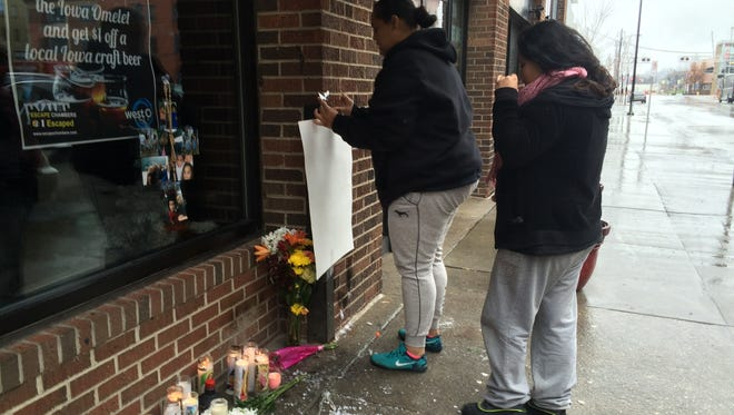 Edmanuel Perez's sister Sindy Sanchez, on left, and his significant other, Carla Garcia  Pizarro, set up a memorial Monday, Nov. 30, 2015, on Third Street in downtown Des Moines, Iowa, near the site where Perez was shot and killed over the weekend.