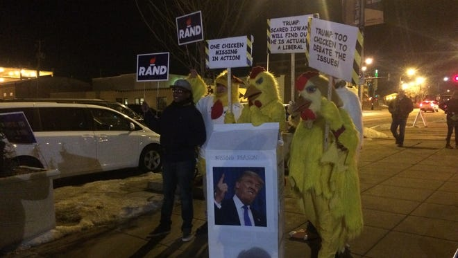 Rand Paul supporters wore chicken suits and held signs insulting presidential candidate Donald Trump for not attending Thursday evening's GOP debate in Des Moines.
