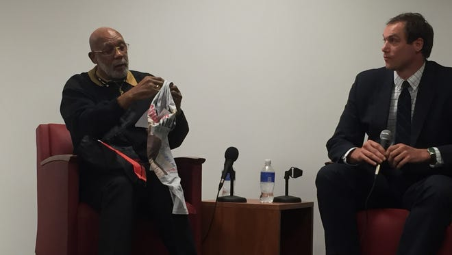 Dr. John Carlos (left)  looks at shirt given to him at Rutgers-Camden during a discussion with students and Stephen Danley.