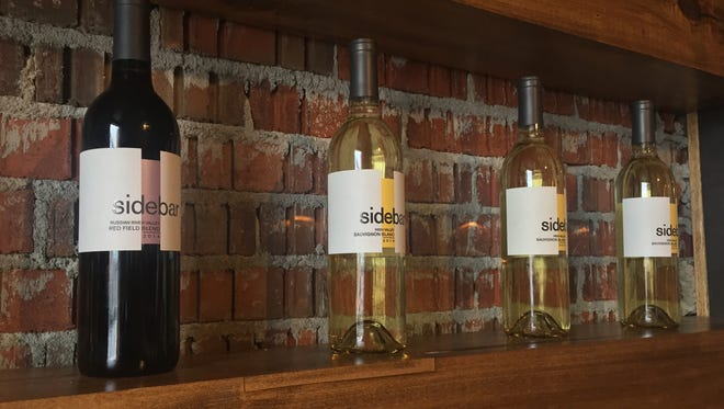 Decorative wine bottles sit on a shelf at the new upscale restaurant Side Bar in East Lansing.