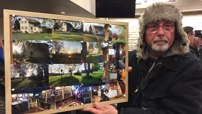 Roger Sturycz, whose home may be taken by eminent domain for the Foxconn factory, holds photos of the property after a hearing Tuesday at Mount Pleasant Village Hall. Sturycz said he has lived at 11604 Highway KR for 15 years.
