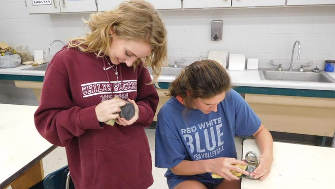 McKenzie Teems and Katie Parmalee clean their pots after they've been fired at Chiles High School.