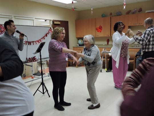 SAGE Manager of Recreation & Volunteer Outreach Susan Wirth and Certified Home Health Aid Venita Stewart dancing with Spend-A-Day clients.