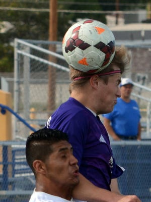 Clovis junior defender Schuyler Houfek keeps the ball in play against Carlsbad junior midfielder Marco Aguilar in the first half Saturday.