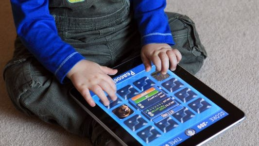 A 13-month-old plays on a tablet.