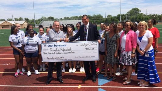 Richard Beckman, CEO of Great Expressions Dental Centers, presented a check for $9,000 to district superintendent George Heitsch and the Farmington High School cheer team.