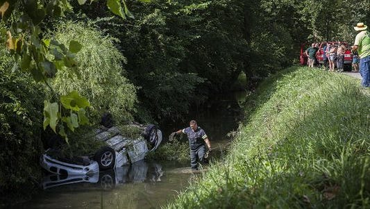 Police respond at the scene of a rollover crash in a creek. The crash involved a driver who allegedly fled from the scene and left a girl and infant trapped in the submerged, overturned vehicle, officials said.