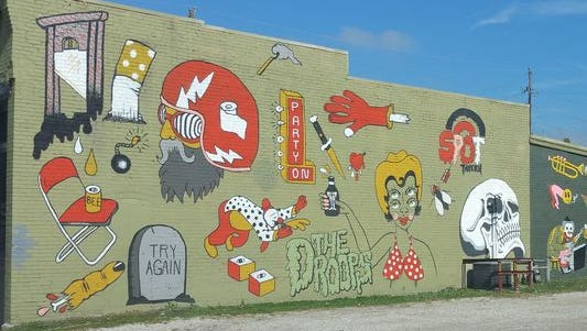 A mural on the side of The Spot Tavern in Lafayette includes a penis in a hotdog bun and a naked woman tied to a tree.