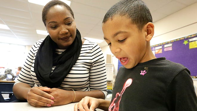 Fond du Lac School District's new equity coach, Shavana Talbert, listens last week to a story being read by Riverside School first-grader Evountaie Burnett-Howard.