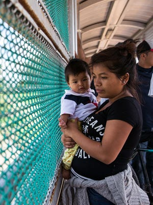 A Guatemalan woman and her child seeking asylum in the United States wait to enter the Mexican side of the international bridge June 27, 2018, at Brownsville, Texas.