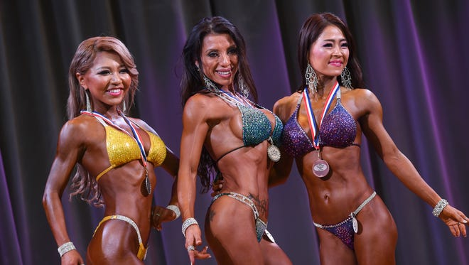 The top three Womens' Bikini International Short class competitors pose for a group picture during the 2016 Michelob Ultra Bodybuilding and Fitness Championships and International Invitational at Leo PalaceResort Guam in Yona on Nov. 12, 2016. From left: Akiko Akimoto, second place, Evelyn Beckwith, first place, and Minako Tanaka, third place.