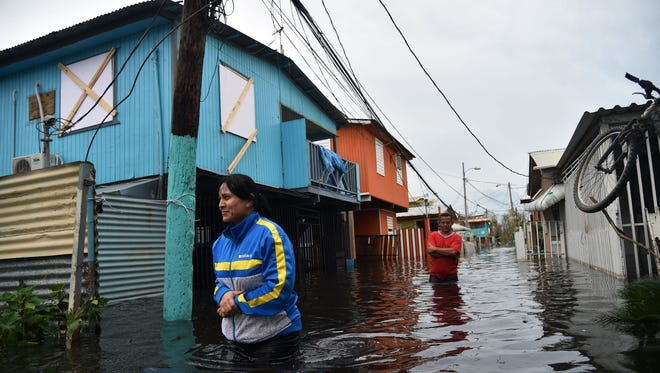 People walk across a flooded street in Juana Matos, Puerto Rico, Sept. 21. The country faced dangerous flooding and an island-wide power outage after Hurricane Maria.
