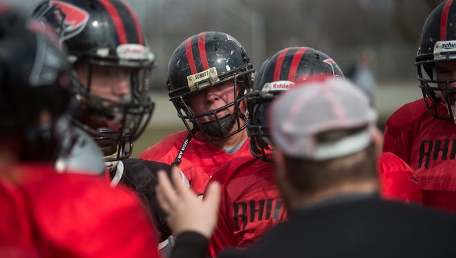 Greg Day, center, and his teammates listen in in the huddle during practice on March 6, 2016.