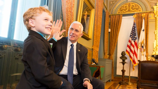 Jordan McLinn, 7, of Indianapolis shares a high-five with Vice President Mike Pence at his ceremonial office in the Eisenhower Executive Office Building on Feb. 7, 2017. McLinn has muscular dystrophy and he and others with serious diseases are lobbying the federal government to allow them to use experimental drugs.