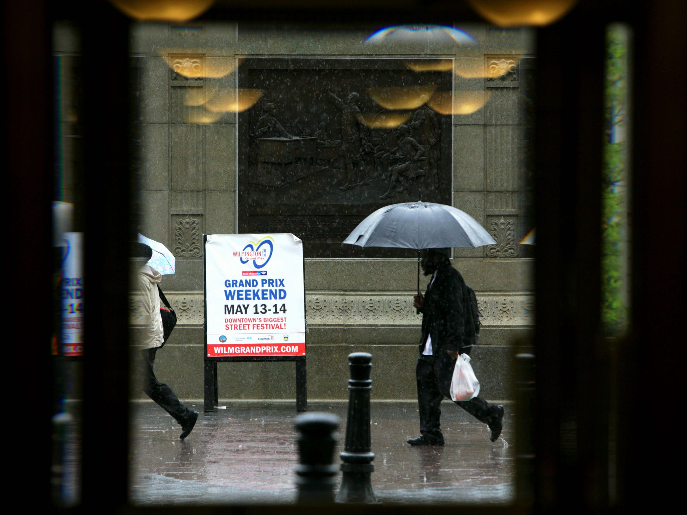 Pedestrians walk by Rodney Square along North Market Street in downtown Wilmington as rain pours down in the area.