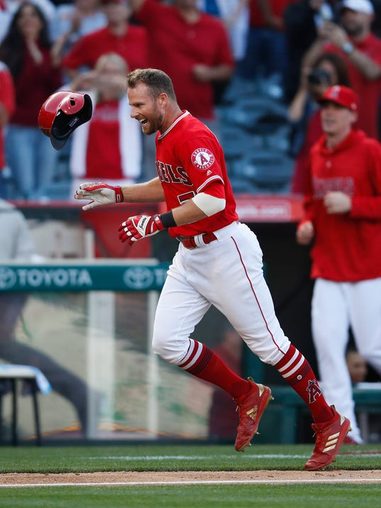 Los Angeles Angels' Zack Cozart tosses helmet while celebrating his walk-off home run against the Cleveland Indians in the 13th inning of a baseball game Wednesday, April 4, 2018, in Anaheim, Calif. The Angels won 3-2. (AP Photo/Jae C. Hong)