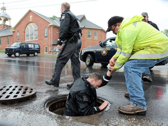 A Dannemora Department of Public Works employee helps a New York State Trooper out of a manhole while searching for two escaped prisoners in Dannemora, N.Y. On Saturday, hundreds of law enforcement personnel have begun an eighth day searching for David Sweat and Richard Matt, two killers who used power tools to cut their way out of Clinton Correctional Facility in Dannemora in northern New York. (Gabe Dickens/The Press-Republican via AP)