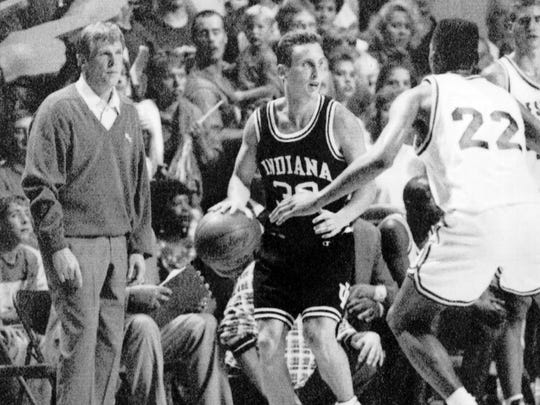 Bobby Hurley, center, brings the ball up the court