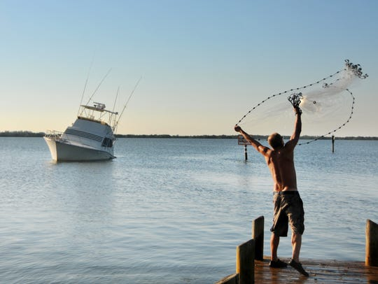 Cocoa Beach resident Tony Anderson throws a cast net off a dock on the Banana River at Bicentennial Park in Cocoa Beach, netting bait fish.