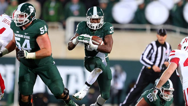 Michigan State Spartans running back Jeremy Langford (33) runs the ball against the Nebraska Cornhuskers defense during the 1st half of a game at Spartan Stadium.