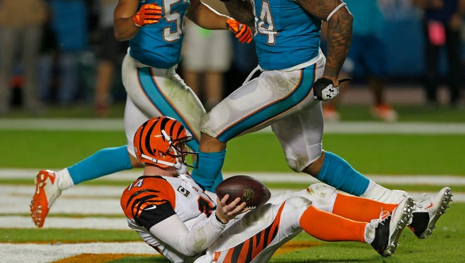 Bengals quarterback Andy Dalton sits in the end zone after being sacked for a safety by the Dolphins' Cameron Wake in overtime at Miami last October.