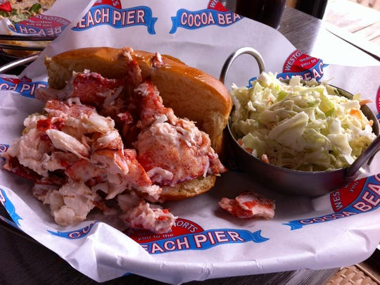 A lot of lobster overflows from a toasted brioche roll on the Lobster Roll ($17.95) at Pelican's at the Cocoa Beach Pier, and you get a pot of house-made slaw with it.