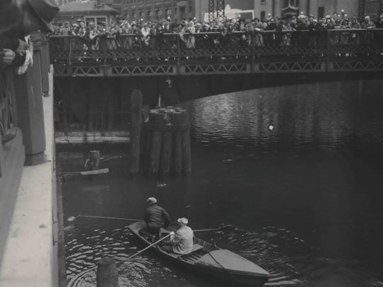 As a crowd watches on the Wisconsin Ave. bridge, bridgetenders Paul Benn (with skimmer) and George De Grace (at the oars) rescue one of the duck hatchlings, nicknamed Black Bill, after the bird left the nest of its mother, Gertie. The mother duck is in the water just above the rowboat. This photo was published in the June 1, 1945, Milwaukee Journal.