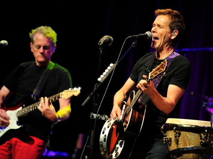 Kevin Bacon, right, and Michael Bacon, of the Bacon Brothers, perform on stage at Franklin Theatre in Franklin, Tenn., Thursday, July 31, 2014.